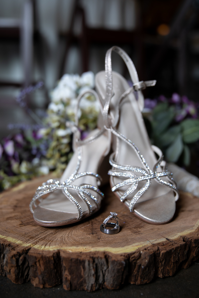 silver and white wedding high heeled shoes sitting on a log with wedding rings perched between them