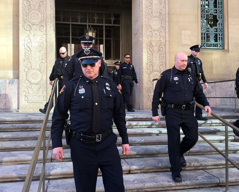 . Officers from the Westerville Police Department in suburban Columbus leave a downtown federal courthouse, Monday, Feb. 12, 2018, in Columbus, Ohio. following the initial appearance by a man accused of providing the gun used to kill two Westerville officers. Suspect Gerald Lawson, accused of providing the weapon, is being held without bond ahead of another hearing Wednesday.  (AP Photo/Andrew Welsh-Huggins)