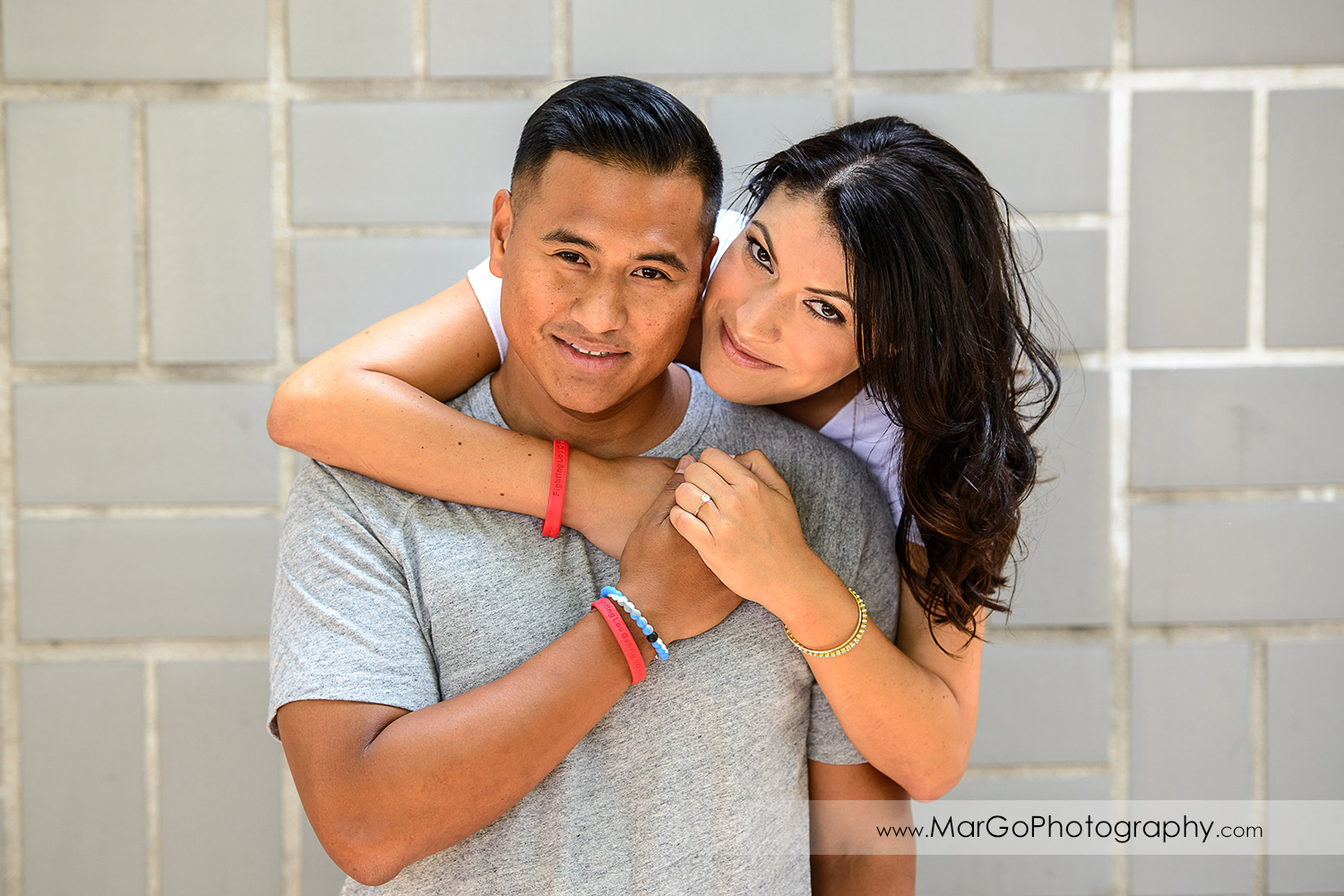 portrait of woman in white blouse hugging man in grey T-shirt on the grey wall looking into camera during engagement session at San Pedro Square Market in San Jose
