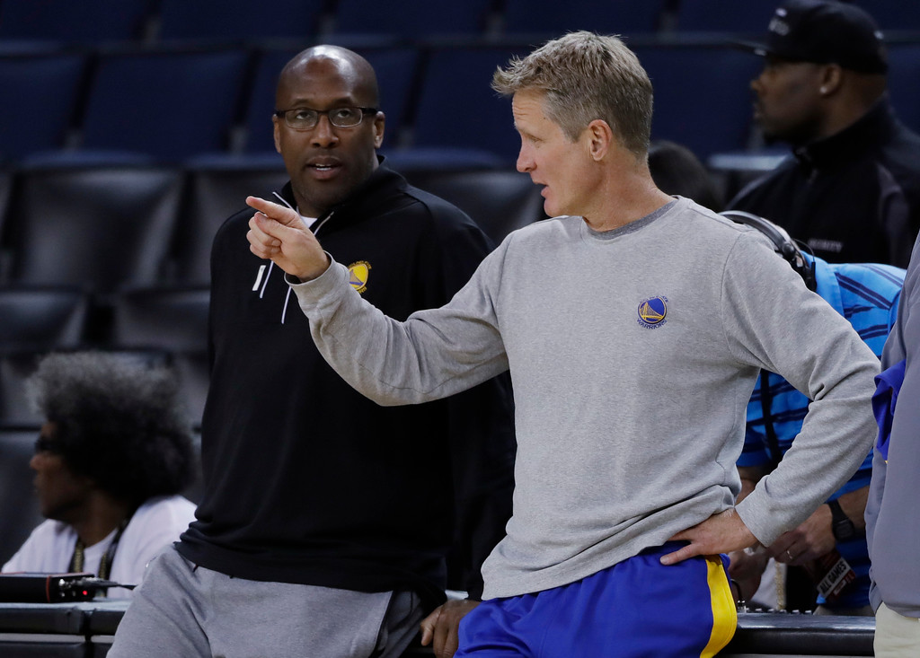 . Golden State Warriors head coach Steve Kerr, right, talks with interim head coach Mike Brown during an NBA basketball practice, Wednesday, May 31, 2017, in Oakland, Calif. The Golden State Warriors face the Cleveland Cavaliers in Game 1 of the NBA Finals on Thursday in Oakland. (AP Photo/Marcio Jose Sanchez)