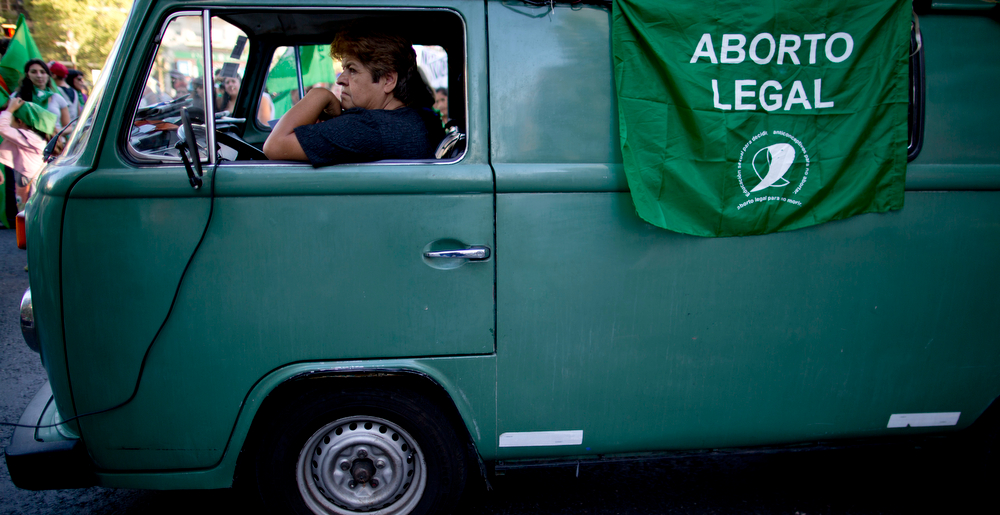 Description of . A woman sits in a van from which a flag hangs that reads in Spanish