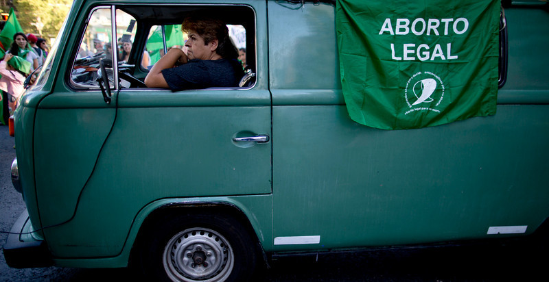 """. A woman sits in a van from which a flag hangs that reads in Spanish \""""Legal Abortion\"""", during a rally in Buenos Aires, Argentina, Friday, March 7, 2014. Supporters of different organizations marched one day ahead of the International Women\'s Day, from Congress to the government house demanding more rights for women. (AP Photo/Natacha Pisarenko)"""