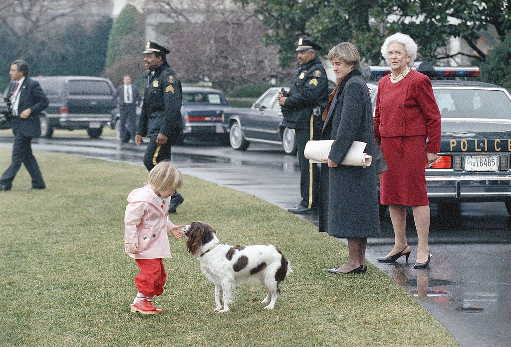 . First lady Barbara Bush watches as her granddaughter Marshall, 2, plays with Bush family dog Millie outside the White House in Washington, Jan. 26, 1989. Marshall\'s godmother Lloyd Hatcher stands next to Mrs. Bush. (AP Photo/J. Scott Applewhite)
