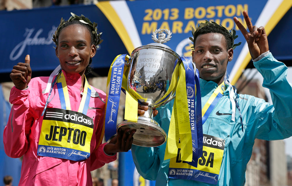 . Rita Jeptoo of Kenya and Lelisa Desisa of Ethiopia pose with a trophy at the finish line after winning the women\'s and men\'s divisions of the 2013 Boston Marathon in Boston Monday, April 15, 2013. (AP Photo/Elise Amendola)