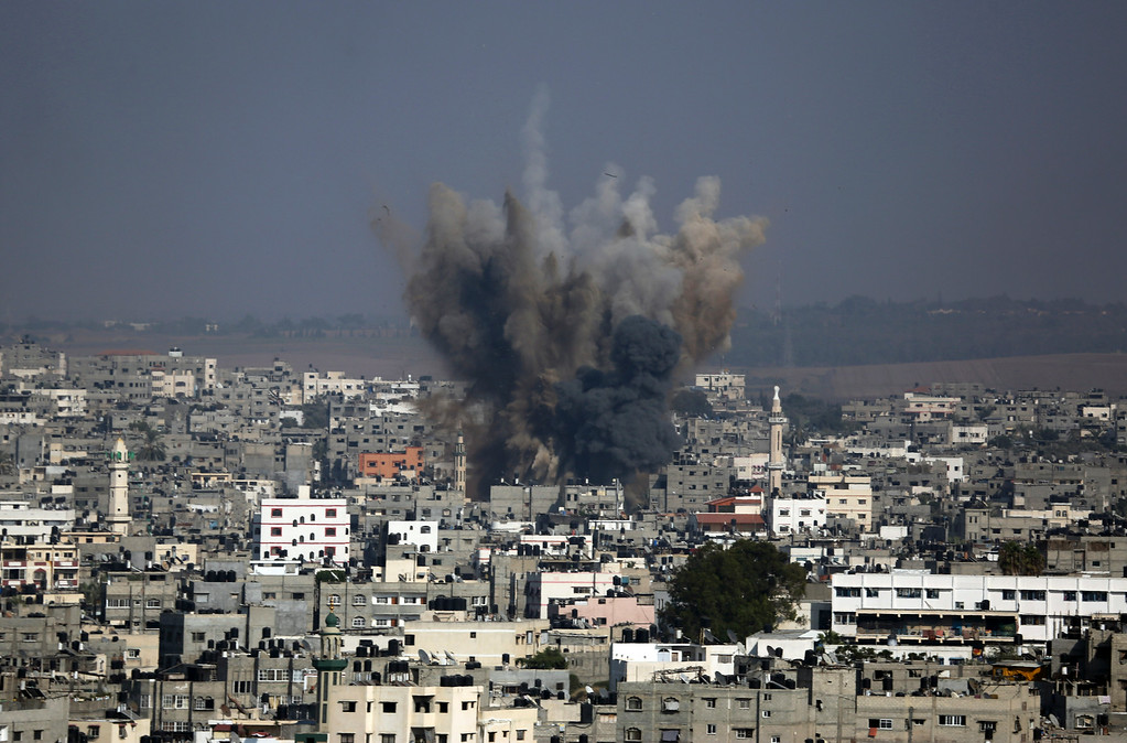 . Smoke and debris from an Israeli strike rise over Gaza City, Tuesday, July 22, 2014, as Israeli airstrikes pummeled a wide range of locations along the coastal area and diplomatic efforts intensified to end the two-week war. (AP Photo/Hatem Moussa)