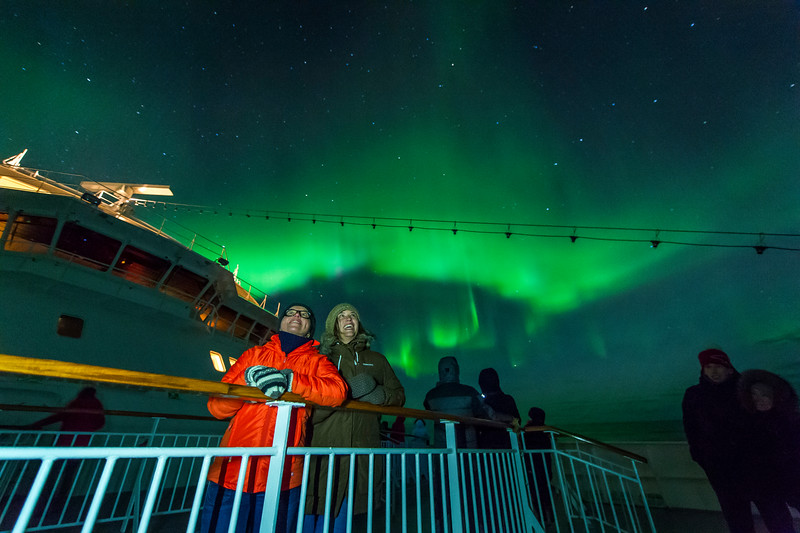Man in a red jacket, woman in a green jacked standing on a ship's deck to see the green northern lights.