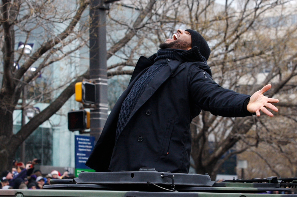 Description of . Baltimore Ravens retiring linebacker Ray Lewis gestures to the crowd gathered on the team's parade route in Baltimore, Maryland February 5, 2013. The Ravens defeated the San Francisco 49ers to win the NFL championship.  REUTERS/Richard Clement