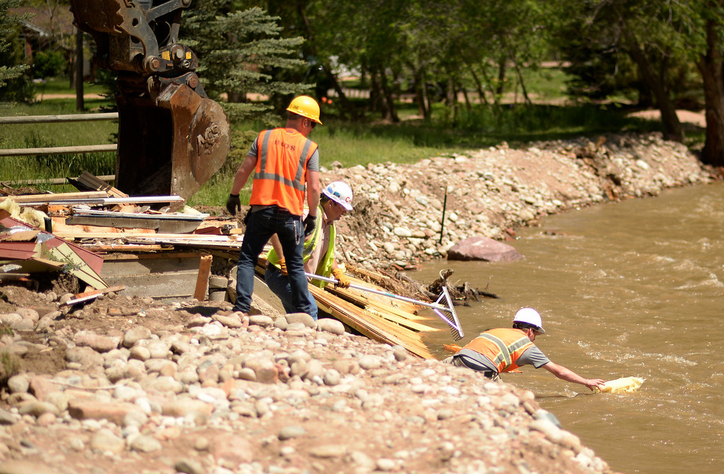 . Crews with Ecoos Environmental and Disaster Restoration keep items from going down the river as they work on demolishing a home in Lyons that was damaged by last years flood, May 27, 2014. (Photo by RJ Sangosti/The Denver Post)