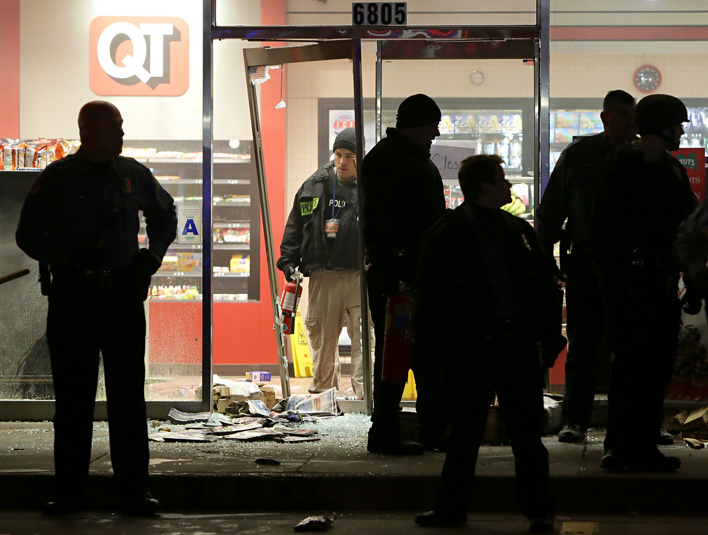 . A police officer with a fire extinguisher stands in the broken out entry to a QuikTrip on Wednesday, Dec. 24, 2014, following a shooting nearby Tuesday in Berkeley, Mo. St. Louis County police say a man who pulled a gun and pointed it at an officer has been killed. (AP Photo/St. Louis Post-Dispatch, David Carson)