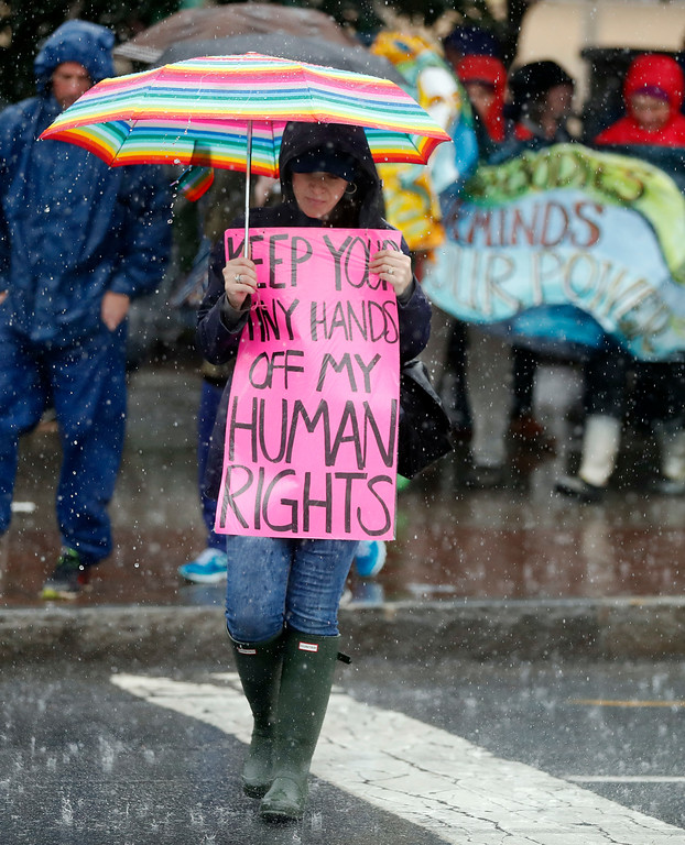 . A woman walks through a heavy downpour before a protest march Saturday, Jan. 21, 2017, in Atlanta. Thousands of people marched through Atlanta one day after President Donald Trump\'s inauguration. (AP Photo/John Bazemore)