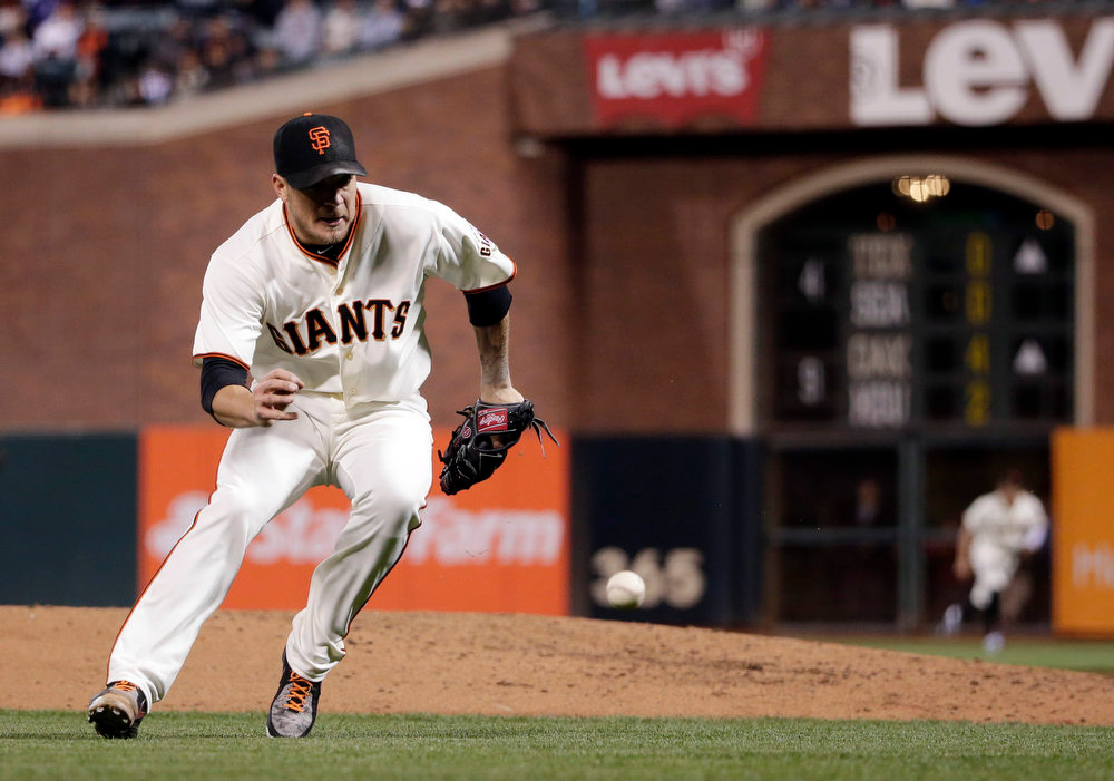 . San Francisco Giants starting pitcher Jake Peavy reaches for a ground ball from Colorado Rockies\' Nolan Arenado during the third inning of a baseball game Monday, Aug. 25, 2014, in San Francisco. Arenado was safe at first base with an infield hit. (AP Photo/Marcio Jose Sanchez)