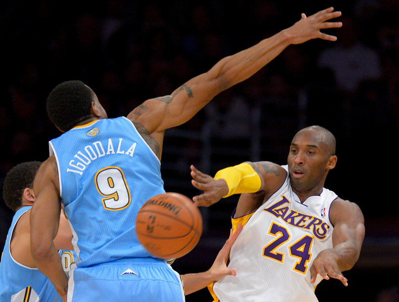 . Los Angeles Lakers guard Kobe Bryant, left, passes around Denver Nuggets guard Andre Iguodala during the first half of their NBA basketball game, Sunday, Jan. 6, 2013, in Los Angeles. (AP Photo/Mark J. Terrill)