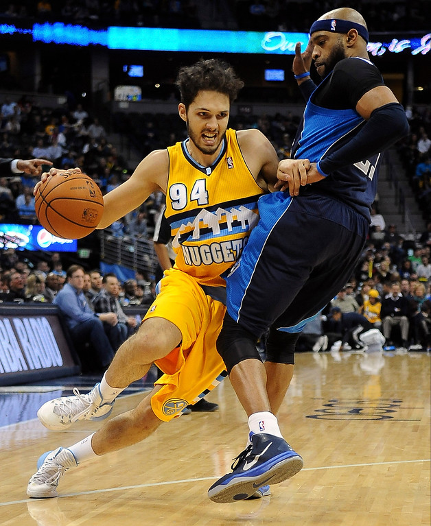 . Denver Nuggets guard Evan Fournier drives to the basket in the first quarter against Vince Carter of the Dallas Mavericks Wednesday night at the Pepsi Center. (Photo By Steve Nehf / The Denver Post)