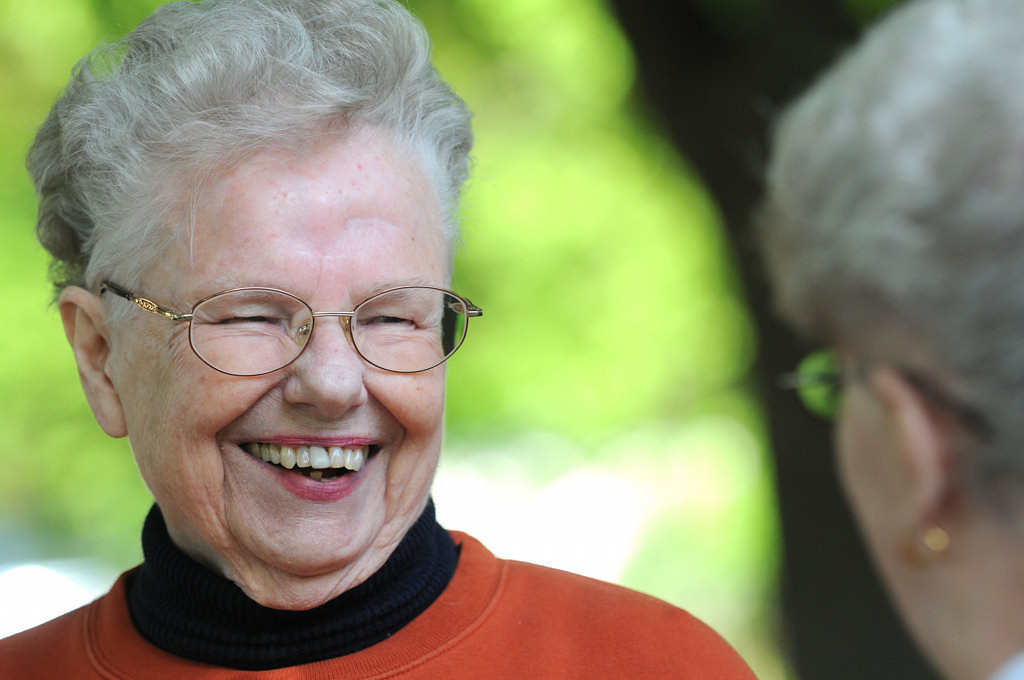 . Opal Kuehn laughs with a neighbor after a crew from Jet-Black resealed her driveway in St. Paul for free on Wednesday May 29, 2013. (Pioneer Press: Jean Pieri)