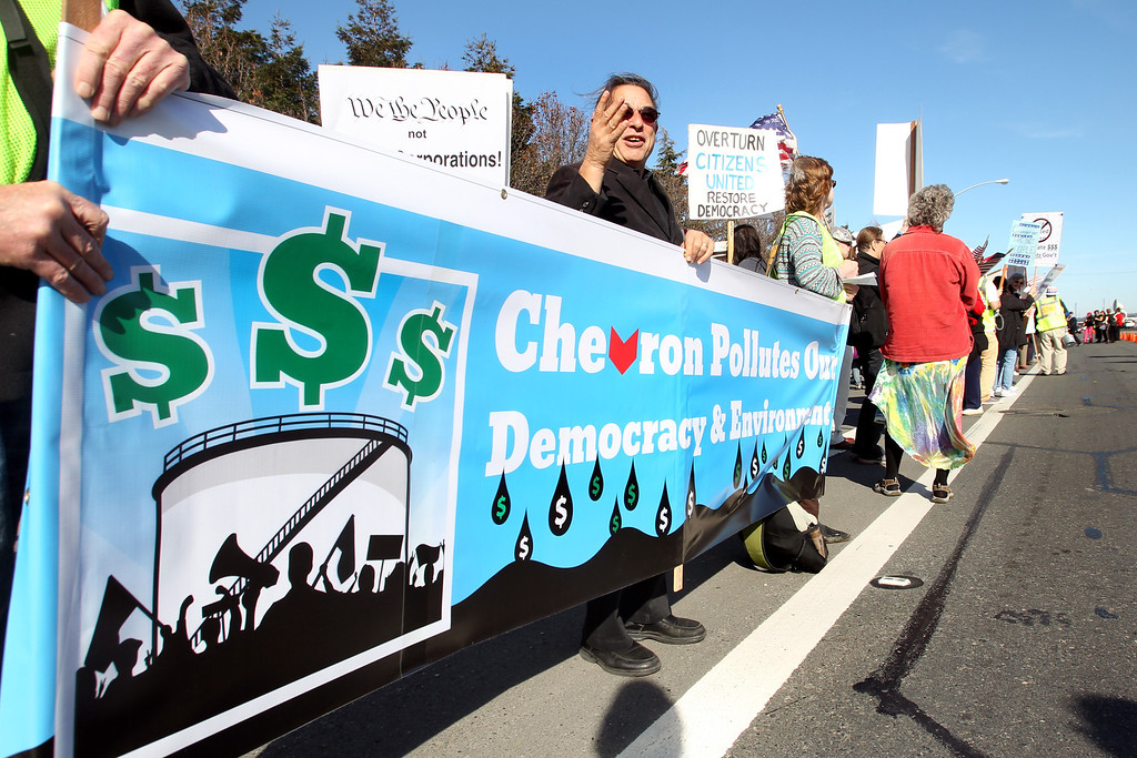 . Demonstrators protest in front of Chevron refinery in Richmond, Calif., on Saturday, Jan. 19, 2013. About 300 people from the nationwide movement called �Money Out, Voters In� demand lawmakers pass measures that limit the corrosive influence of money in politics and expand democratic participation at the polls. Chevron donated substantial amounts of money to both local and national campaigns attempting to influence all levels of government.(Ray Chavez/Staff)