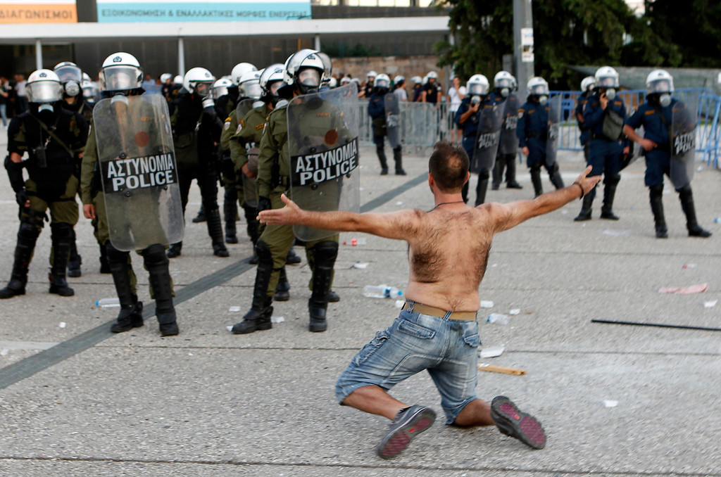 . A protester confronts riot police guarding the entrance to Thessaloniki\'s International Trade Fair during a protest against austerity September 10, 2011.  REUTERS/Yannis Behrakis