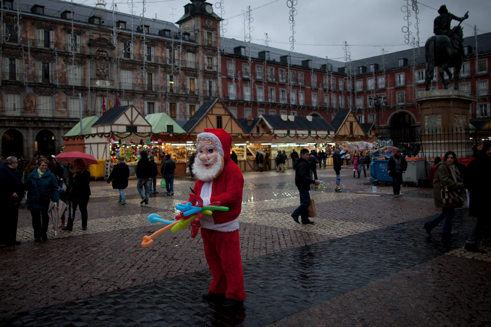 Description of . A person dressed as Santa Claus sells balloons at the Christmas market fair in Plaza Mayor Square on December 14, 2012 in Madrid, Spain. Many businesses are starting sales and discounts before Christmas to try and gain customers during the current economic crisis.  (Photo by Pablo Blazquez Dominguez/Getty Images)