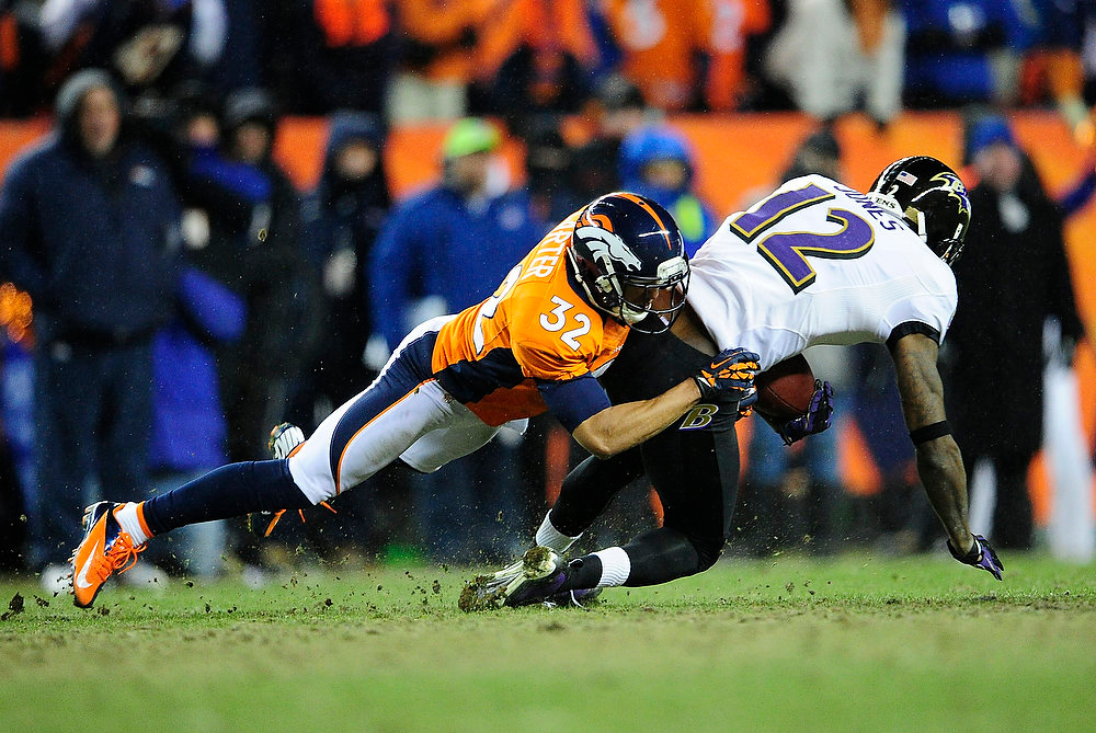 . Denver Broncos defensive back Tony Carter (32) takes down Baltimore Ravens wide receiver Jacoby Jones (12). The Denver Broncos vs Baltimore Ravens AFC Divisional playoff game at Sports Authority Field Saturday January 12, 2013. (Photo by AAron  Ontiveroz,/The Denver Post)