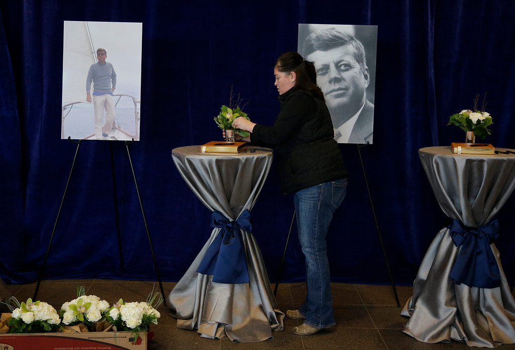 . A woman arranges flowers at the sign in tables in the John F. Kennedy Presidential Library and Museum before visitors arrive Friday Nov. 22, 2013 in Boston. Kennedy, the 35th President of the United States, was assassinated in Dallas 50 years ago today. (AP Photo/Stephan Savoia)