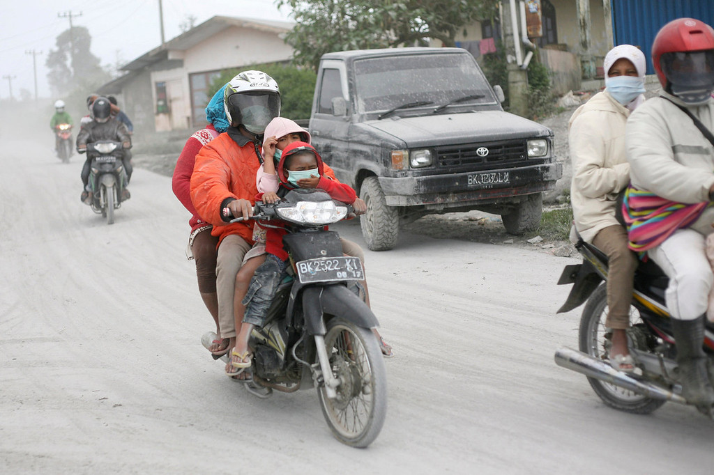 . Villagers ride motorcycles on a road covered by volcanic ash from the eruption of Mount Sinabung as they flee their homes in Karo, North Sumatra, Indonesia, Sunday, Sept. 15, 2013. Thousands of people fled their homes after the volcano erupted early Sunday.   (AP Photo/Binsar Bakkara)