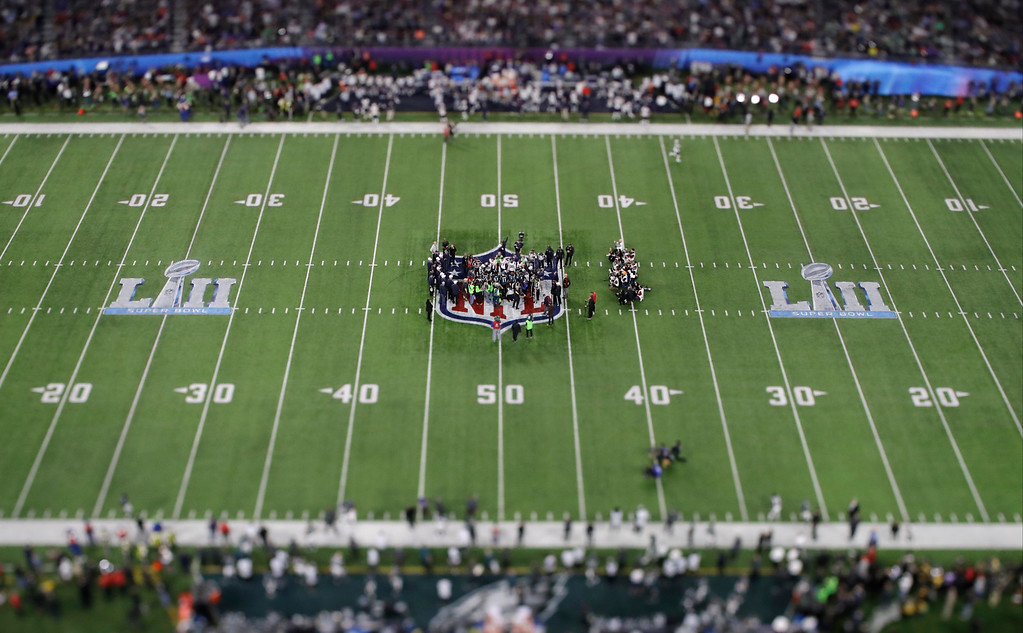 . In this picture made with a specialty lens the Philadelphia Eagles and the New England Patriots gather for the coin toss before a NFL Super Bowl 52 football game Sunday, Feb. 4, 2018, in Minneapolis. (AP Photo/Matt Slocum)