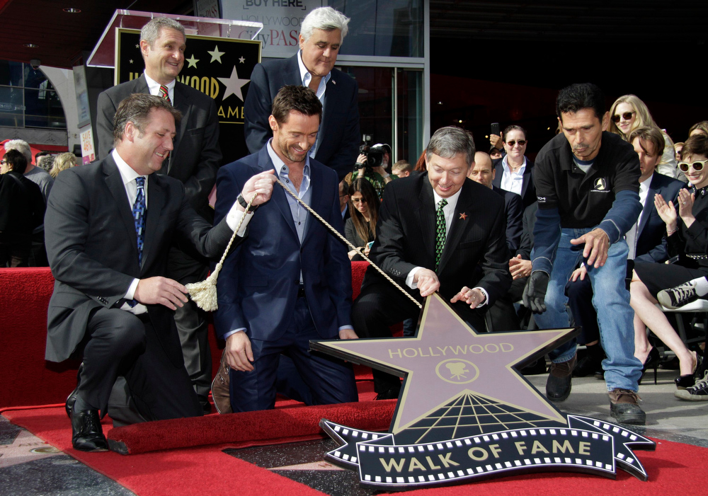 Description of . Actor Hugh Jackman (bottom 2nd L) is presented with a star on the Hollywood Walk of Fame in Hollywood, California, December 13, 2012. REUTERS/Jonathan Alcorn
