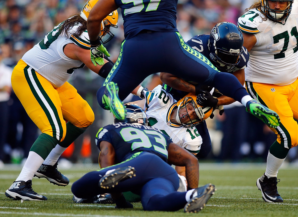 . SEATTLE, WA - SEPTEMBER 04:  Quarterback Aaron Rodgers #12 of the Green Bay Packers is tackled by defensive end O\'Brien Schofield #93 of the Seattle Seahawks during the first quarter of the game at CenturyLink Field on September 4, 2014 in Seattle, Washington.  (Photo by Jonathan Ferrey/Getty Images)
