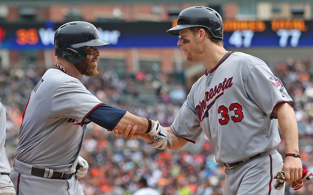 . Minnesota\'s Ryan Doumit, left, is congratulated by teammate Justin Morneau after hitting a three-run home run in the fifth inning.  (Photo by Leon Halip/Getty Images)