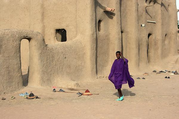 A girl walks past a mosque in a village near Djenne, Mali