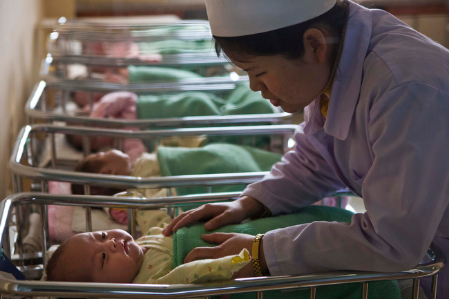 . A North Korean nurse comforts a baby at a nursery inside Pyongyang Maternity Hospital in Pyongyang, North Korea on Wednesday, Feb. 20, 2013. (AP Photo/David Guttenfelder)