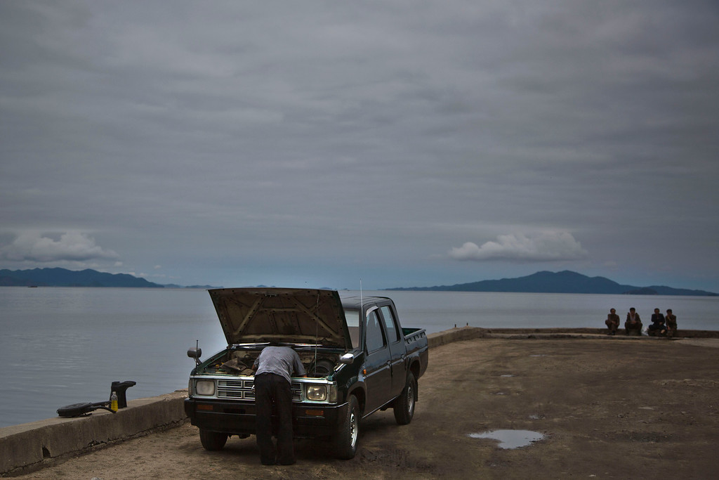 """. In this June 21, 2014 photo, a man works on his car as others sit next to the sea Wonsan, North Korea. The Associated Press was granted permission to embark on a weeklong road trip across North Korea to the countryís spiritual summit Mount Paektu. The trip was on North Korea\'s terms.  An AP reporter and photographer couldn\'t interview ordinary people or wander off course, and government \""""minders\"""" accompanied them the entire way.  (AP Photo/David Guttenfelder)"""