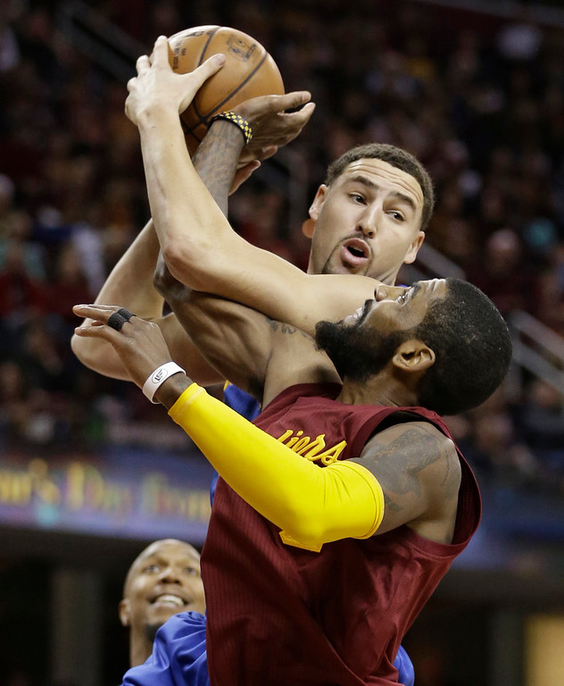 . Golden State Warriors\' Klay Thompson looks to pass over Cleveland Cavaliers\' Kyrie Irving, right, in the first half of an NBA basketball game, Sunday, Dec. 25, 2016, in Cleveland. (AP Photo/Tony Dejak)