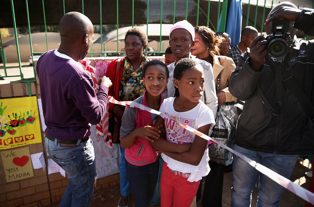 . PRETORIA, SOUTH AFRICA - JUNE 25:  People gather to watch television news reporters outside of the Mediclinic Heart Hospital where former South African President Nelson Mandela is being treated June 25, 2013 in Pretoria, South Africa. South African President Jacob Zuma confirmed Sunday that Mandela\'s condition has become critical since he was admitted to the hospital over two weeks ago for a recurring lung infection.  (Photo by Chip Somodevilla/Getty Images)