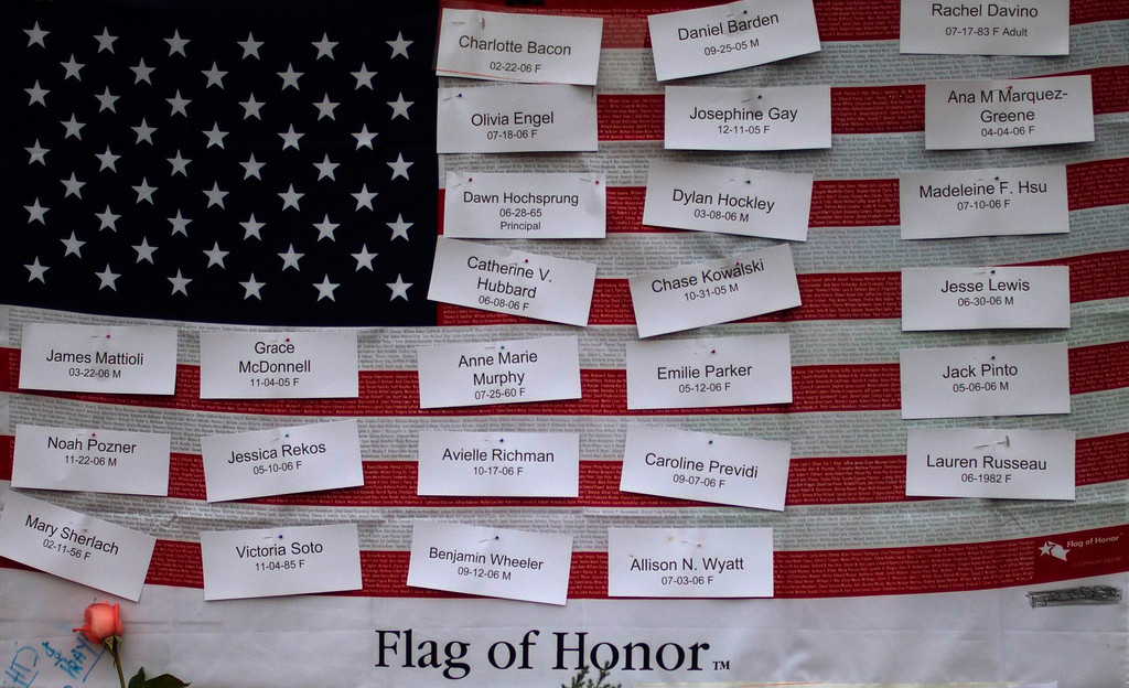 . The names of the victims of the Sandy Hook Elementary shooting are seen on an U.S. flag in the town center of Sandy Hook Village in Newtown, Connecticut December 16, 2012. Worshippers filled Sunday services to mourn the victims of a gunman\'s elementary school rampage that killed 20 children and six adults with the president due to appear later at an interfaith vigil to help this shattered Connecticut town recover.   REUTERS/Adrees Latif