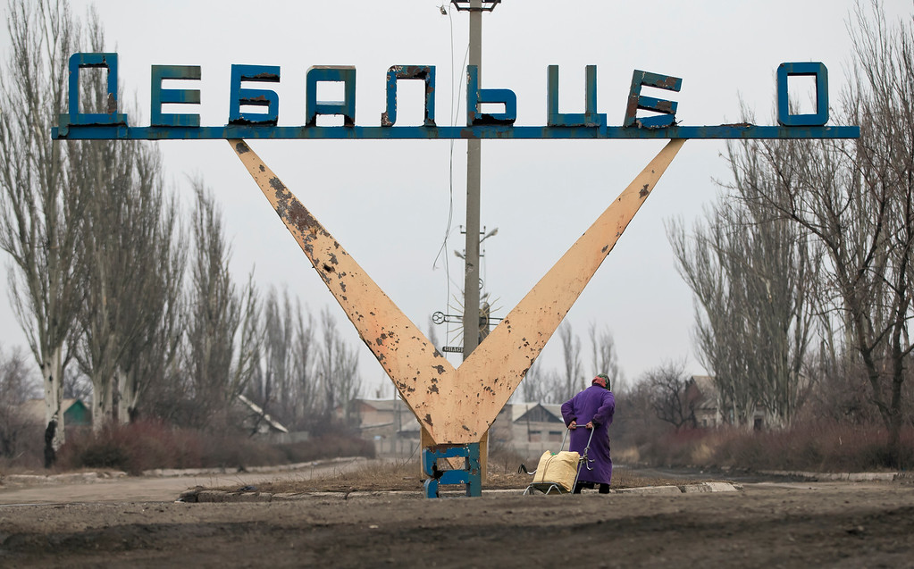 . An elderly woman drags a cart with belongings on the outskirts of Debaltseve, Ukraine, Thursday, Feb. 26, 2015. After weeks of relentless fighting, which inflicted severe damage to most buildings the embattled Ukrainian rail hub of Debaltseve fell last week to Russia-backed separatists. (AP Photo / Vadim Ghirda)