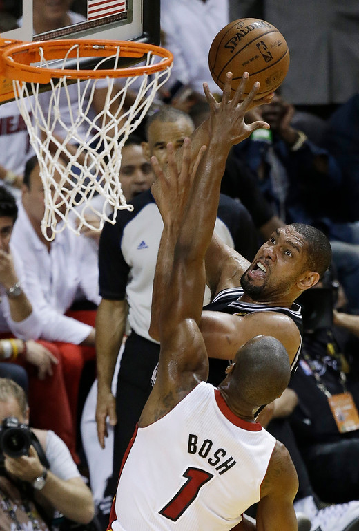 . The San Antonio Spurs\' Tim Duncan (21) shoots over Miami Heat\'s Chris Bosh (1) during the second half in Game 7 of the NBA basketball championships, Thursday, June 20, 2013, in Miami. (AP Photo/Wilfredo Lee)