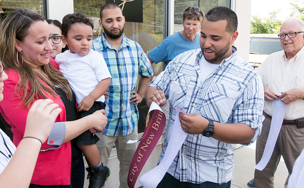 08/29/18 Wesley Bunnell | Staff J's Auto Sales and Repair LLC located at 866 West Main St in New Britain held a ribbon cutting for their official opening on Wednesday afternoon. Minerva Cardona holds son Jace Ruiz, age 2, as husband and shop owner Jesus Ruiz folds up the New Britain ribbon.
