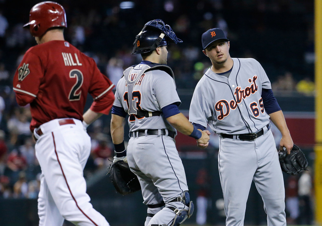 . Detroit Tigers\' Blaine Hardy (65) shakes hands with catcher Alex Avila as Arizona Diamondbacks\' Aaron Hill runs to the dugout after the final out of a baseball game, Wednesday, July 23, 2014, in Phoenix. The Tigers won 11-5. (AP Photo/Matt York)