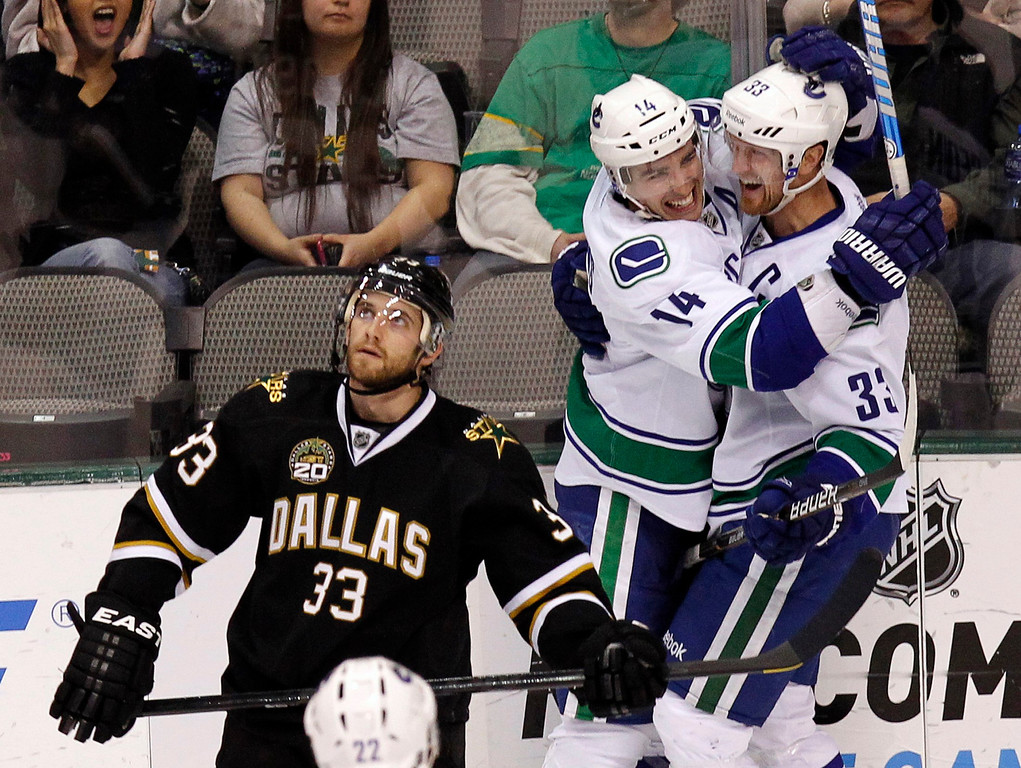 . Vancouver Canucks Alexandre Burrows (14) and Henrik Sedin (33) celebrate Henrik\'s goal as Dallas Stars Alex Goligoski skates past during the third period of their NHL hockey game in Dallas, Texas February 21, 2013.  REUTERS/Mike Stone