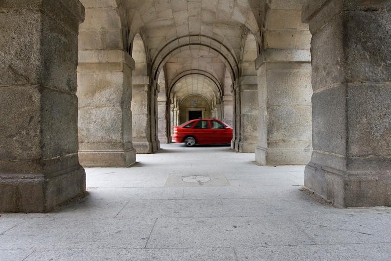 Contrasting image of a car through a 16th century arcade. Spain
