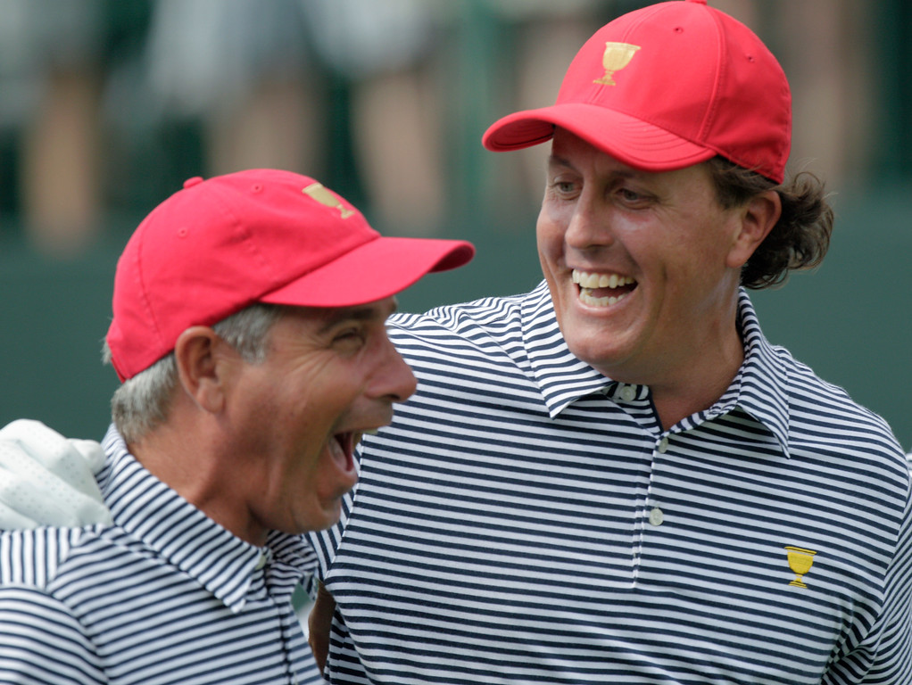 . United States\' Phil Mickelson, right, and team captain Fred Couples laugh together while walking down the first tee during a foursome match against the International team at the Presidents Cup golf tournament at Muirfield Village Golf Club Friday, Oct. 4, 2013, in Dublin, Ohio. (AP Photo/Jay LaPrete)