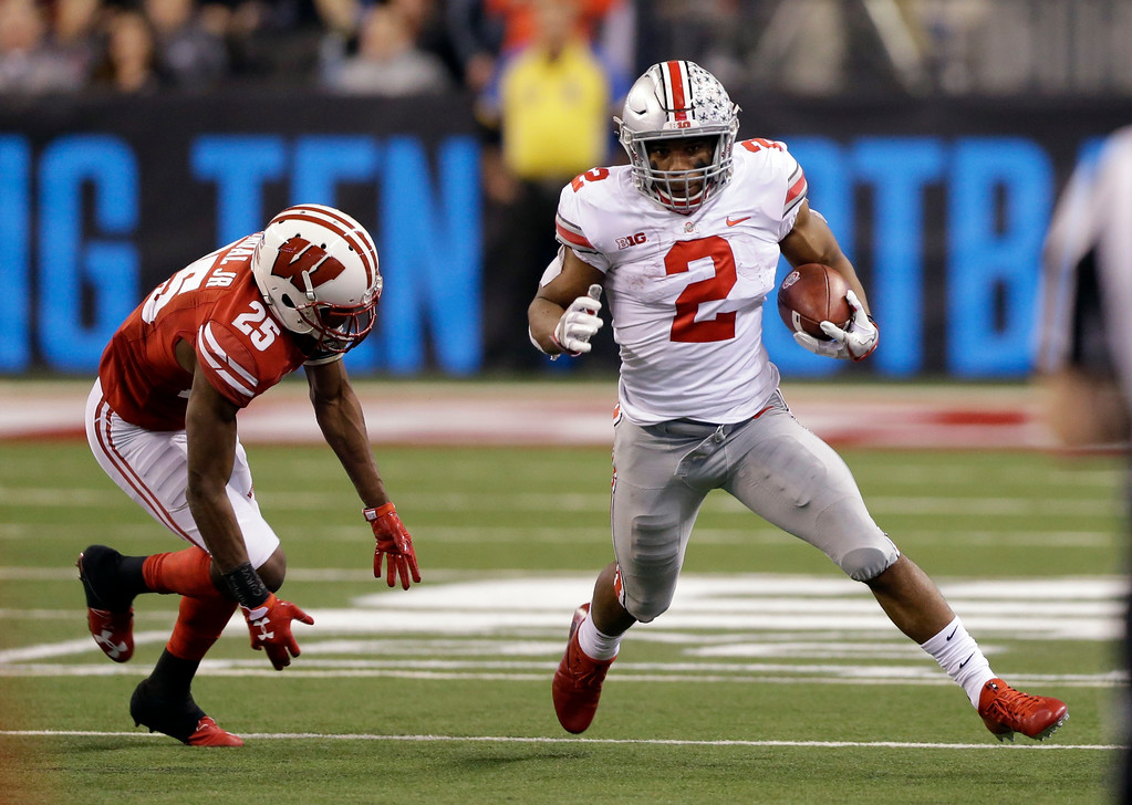 . Ohio State running back J.K. Dobbins, right, runs with the ball past Wisconsin cornerback Derrick Tindal during the second half of the Big Ten championship NCAA college football game, Saturday, Dec. 2, 2017, in Indianapolis. (AP Photo/AJ Mast)