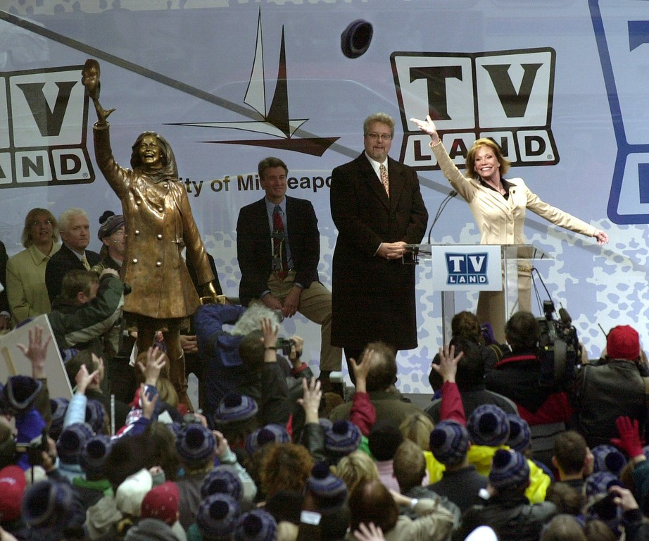 ". Mary Tyler Moore, right, tosses her hat out to the crowd after the a bronze statue of her famous hat toss, left, was unveiled Wednesday, May 8, 2002, on the Nicollet Mall in downtown Minneapolis.  A host of thousands of people gathered to see the statue which captures Moore tossing her hat in the intersection where she originally twirled around in the opening of her 1970s hit television series ""The Mary Tyler Moore Show.\""  (AP Photo/Dawn Villella)"
