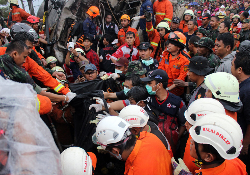. Rescue foprces try to evacuate bodies of victims from a collided commuter train in Jakarta, Indonesia, 09 December 2013. At least six people died after a fuel truck hit by commuter train in Jakarta.  EPA/ADI WEDA