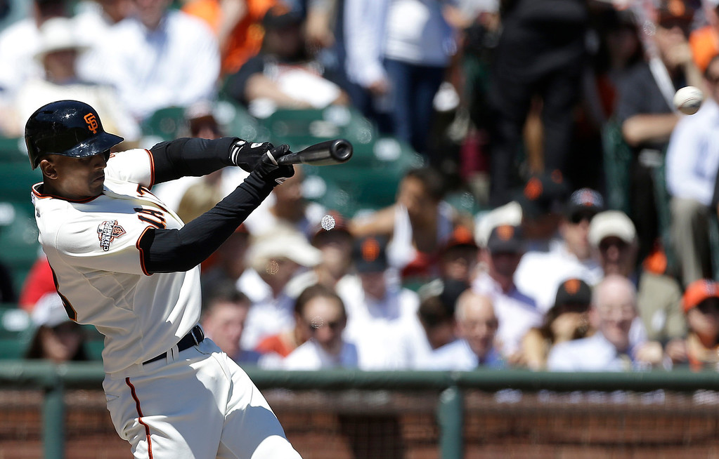 . San Francisco Giants\' Joaquin Arias singles off of Colorado Rockies pitcher Jeff Francis to score Buster Posey during the first inning of a baseball game in San Francisco, Wednesday, April 10, 2013. (AP Photo/Jeff Chiu)