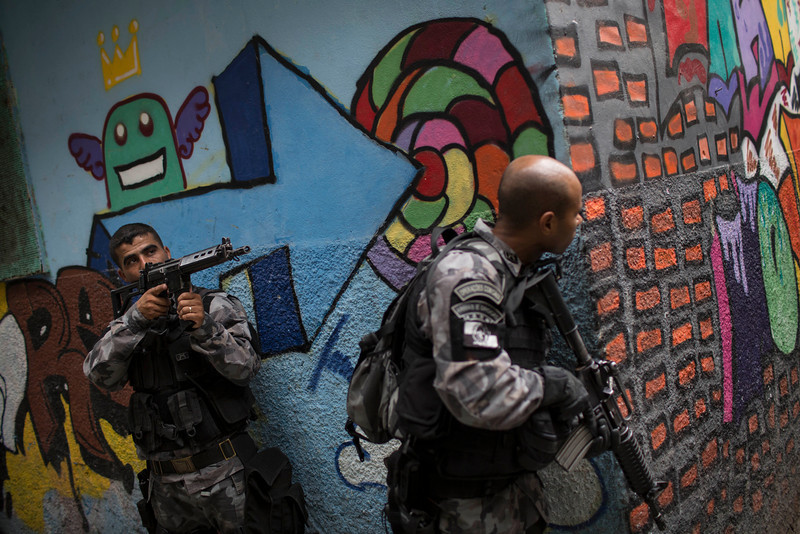 """. Military police officers patrol during an operation in the Mare slum complex, ahead of its \""""pacification,\"""" in Rio de Janeiro, Brazil, Tuesday, March 25, 2014. (AP Photo/Felipe Dana)"""