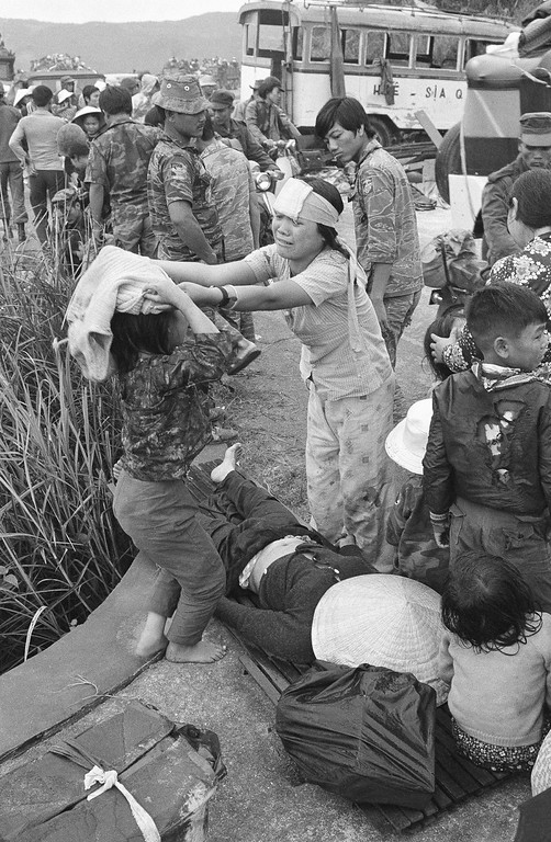 . Injured victims of a road accident in the panicky flight from Hue stand over a dead woman in Hai Van Pass, March 21, 1975. Fatal accidents and injuries were common among the thousands of refugees who fled advancing North Vietnamese, and attempted to find refuge in the coastal city of Da Nang. (AP Photo)