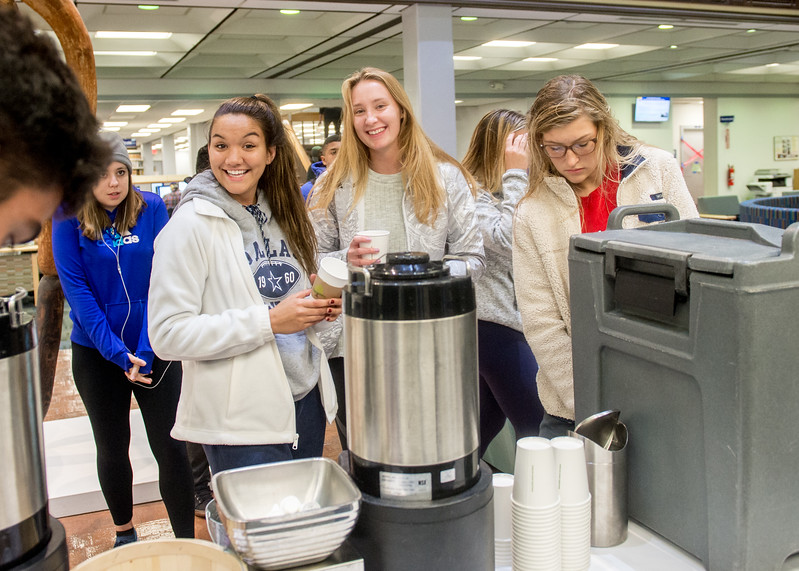 Students enjoy the free begal and hot beverage as a support for their final exam preparation in Mary and Jeff Bell Library.