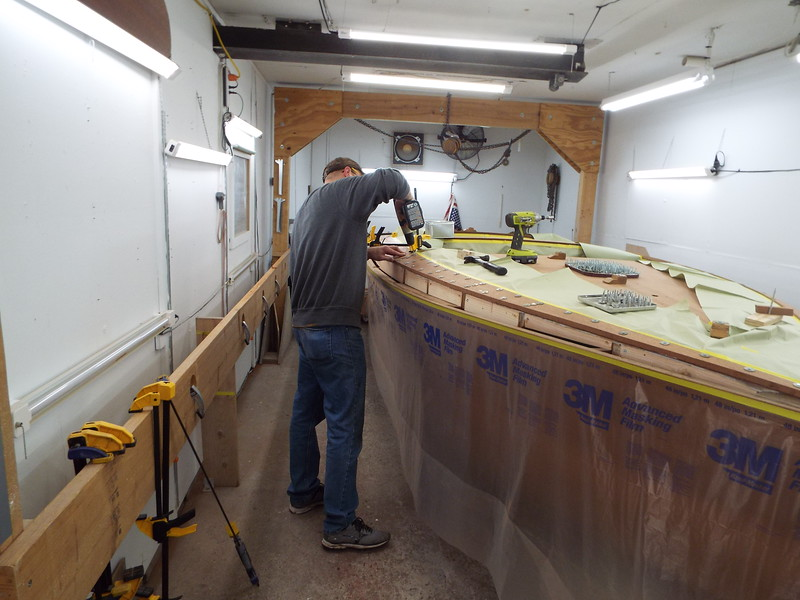 Installing temporary fasteners to hold the cover in place until the epoxy cures.