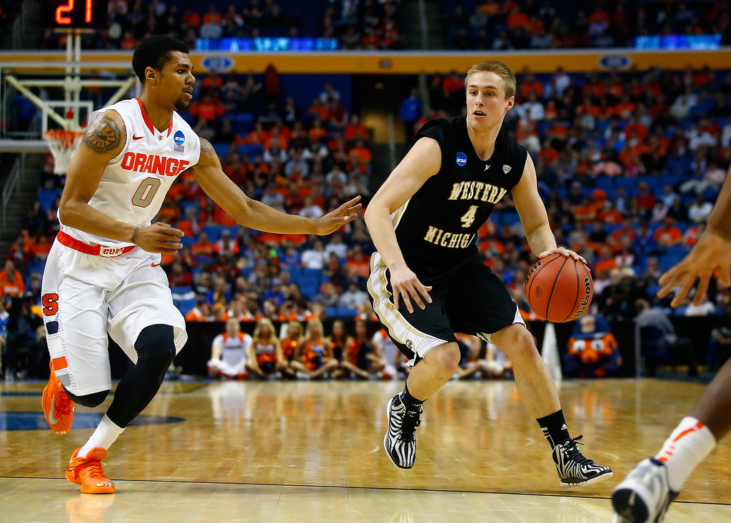 . BUFFALO, NY - MARCH 20: Jared Klein #4 of the Western Michigan Broncos drives to the basket as Michael Gbinije #0 of the Syracuse Orange defends during the second round of the 2014 NCAA Men\'s Basketball Tournament at the First Niagara Center on March 20, 2014 in Buffalo, New York.  (Photo by Jared Wickerham/Getty Images)